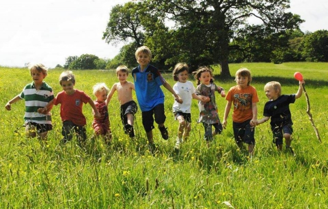 children running through long grass